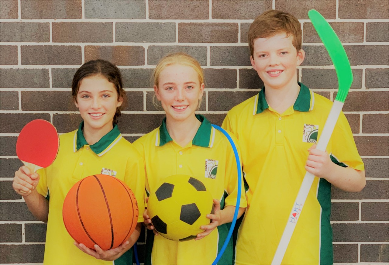 Three students in PE uniform holding sports equipment